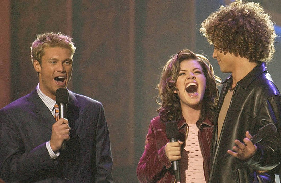 Kelly Clarkson reacts to Ryan Seacrest's announcement that she won Season 1 of American Idol while Justin Guarini looks on. (FOX Photo)